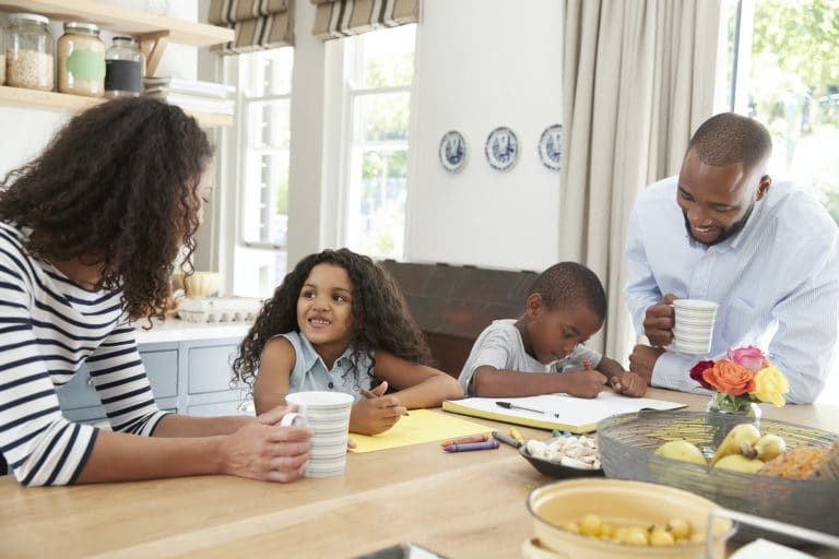 Young black family together in their kitchen, close up