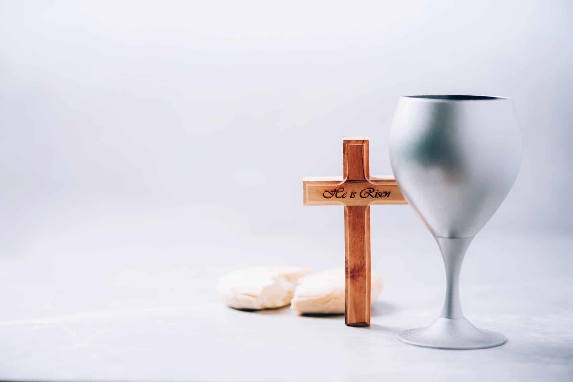 Communion still life. Unleavened bread, chalice of wine on grey background. Christian communion